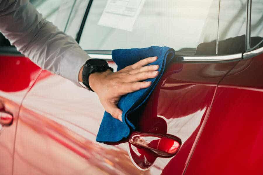 Mann putzt seinen schwarzen Sportwagen.